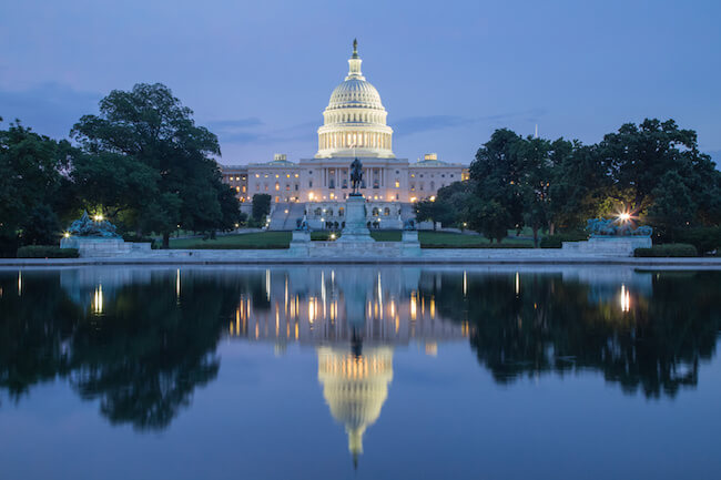 a view of the US capitol building at dusk across the reflecting pool