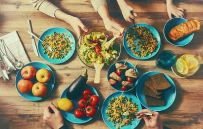 people reach for plates around a table filled with food