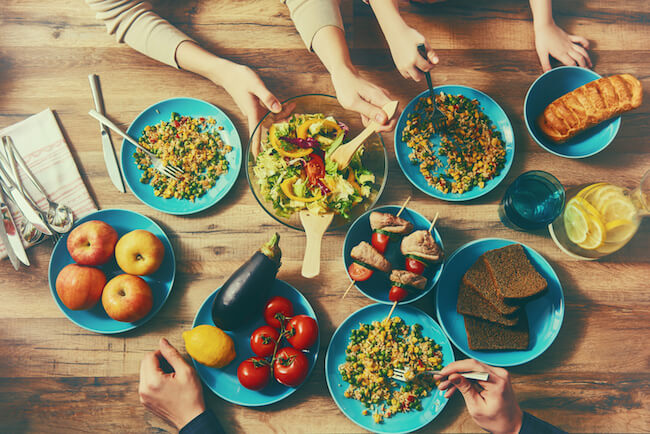 hands reach for bowls around a table filled with food