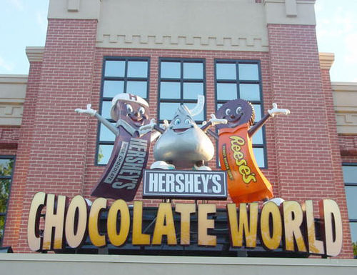 the entrance to chocolate world in hershey pennsylvania, featuring a hershey bar, a hershey's kiss, and a reese's peanut butter cup