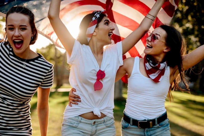 friends hold an american flag and smile during an independence day celebration