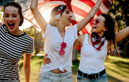 friends hold an american flag on a sunny evening