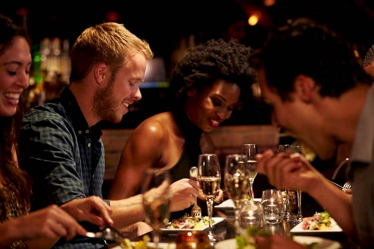 Group of diverse young friends eating dinner