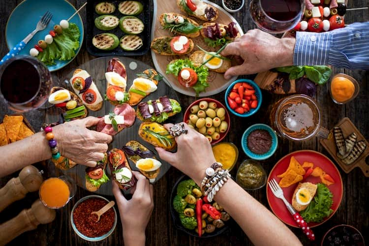 People's hands reaching for plates of tapas
