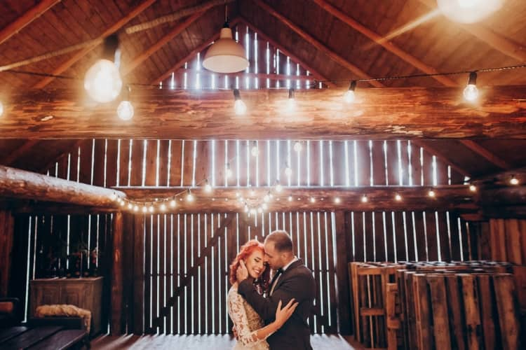 A couple is dancing at a barn wedding
