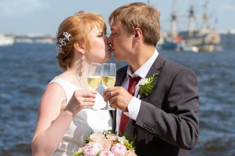 A couple is kissing after a champagne toast