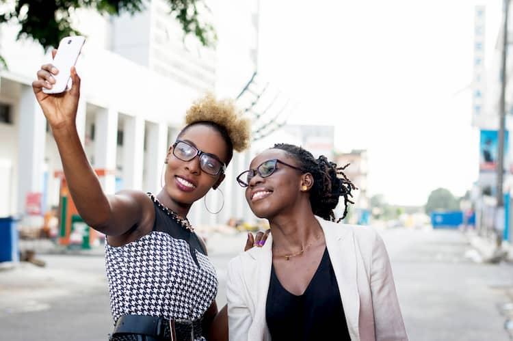 Two women taking selfie in city street