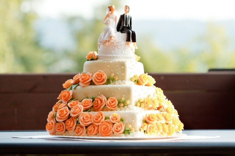 A white wedding cake with an intricate floral design