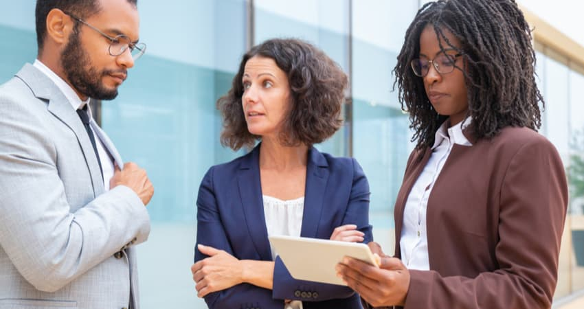 Three people discussing business over a tablet