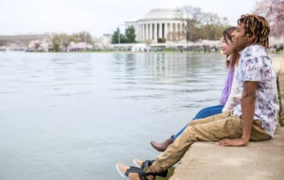 Two people sitting along the Tidal Basin in Washington DC