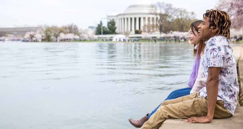 Two people sitting along the Tidal Basin in Washington DC