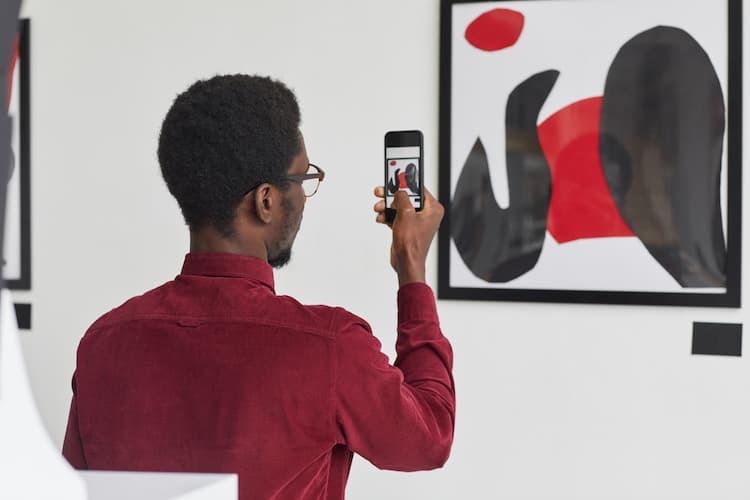 Man taking photo of art in gallery