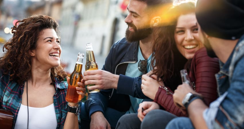 Four friends sit in an outdoor dining space and smile over bottles of beer