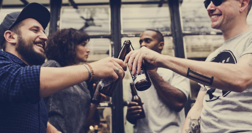 Four friends toast with bottles of beer in an industrial warehouse