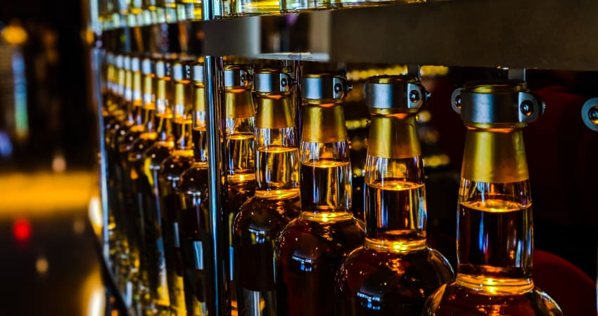 A row of bottles filled with amber-colored drinks in a dark metal mechanism