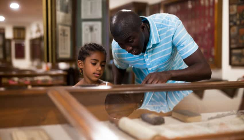 A father and child looking at exhibits in a museum