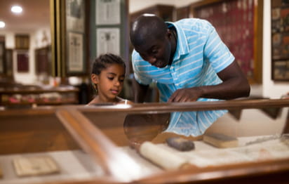 A father and child looking at a museum exhibit