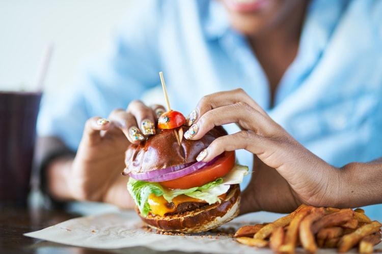 a restaurant patron picks up a burger and prepares to take a bite