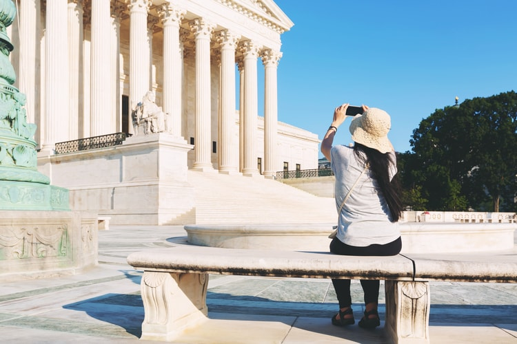 a woman points her phone towards the supreme court building to take a picture