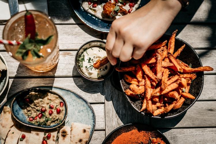 a restaurant patron dips fries into a sauce