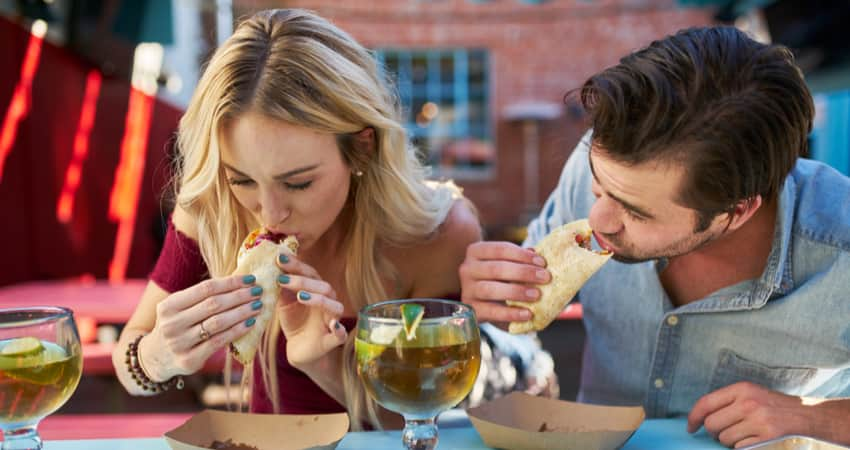 Two people eating tacos with cocktails